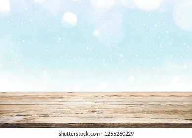 Wood table top on winter snow and white bokeh abstract background and used for montage or display products.