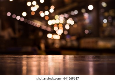 Wood table top with reflect on blur of lighting in night cafe,restaurant background/selective focus.