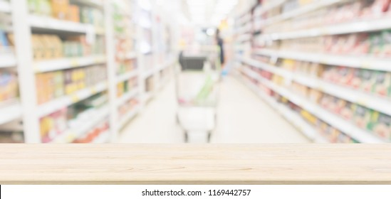 Wood table top with supermarket aisle blur background for product display