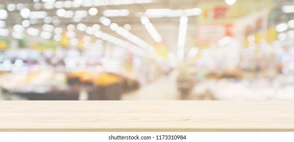 Wood table top with supermarket grocery store blurred defocused background with bokeh light for product display