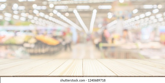 Wood table top with supermarket grocery store blurred defocused panorama background with bokeh light for product display