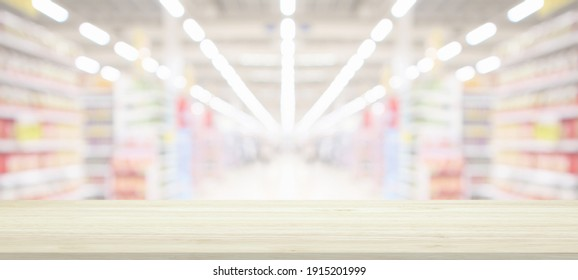 Wood table top with supermarket grocery store blurred background with bokeh light for product display