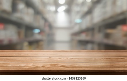 Wood table in warehouse storage blur background with empty copy space on the table for product display mockup. Hardware goods distribution and industrial logistics concept.
