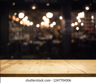 wood tabletop counter display product with abstract bokeh blur nigh restaurant for background