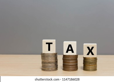 Wood tax and money coin stack on wooden table background.  Tax Day takes place on April 15,2019