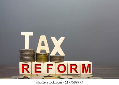 Wood  tax reform word and money coin stack on wooden table gary background. concept tax payments will be chang.