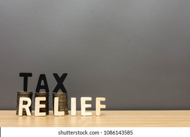 Wood  tax relief word and money coin stack on wooden table background. Tax savings literacy concept.