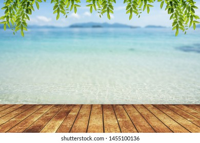 wood terrace over blue sea and tropical island beach background.