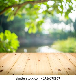 Wood terrace over blur nature view of green leaf on blurred greenery background in garden