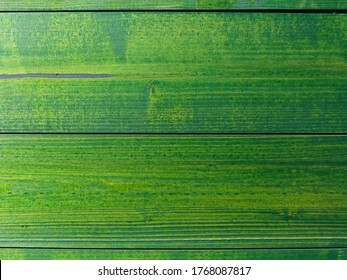 wood texture background. Stained green fence wooden planks. pine wood with joint and wood grain. construction material. wood texture and patter. wooden fence. horizontal slats. close-up view.