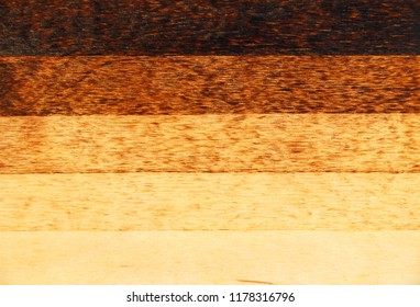 Wood texture. Pyrography on plywood. Wooden background with scorched stripes of different shades.