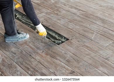 Wood Textured Ceramic Tiles. Tiler placing ceramic floor tile with mortar in position over adhesive with lash tile leveling system.