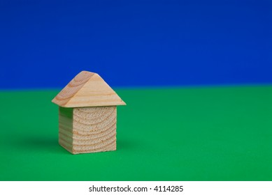 Wood toy block house on the blue and green background