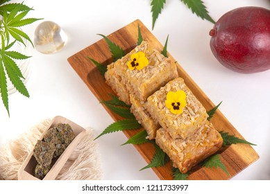 Wood tray with Cannabis infused blondies isolated on white background- medical marijuana edibles concept