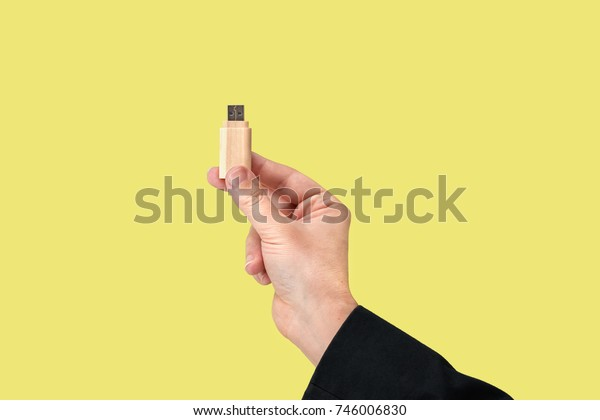 Wood USB Flash drive on hand with isolated yellow background. Front view