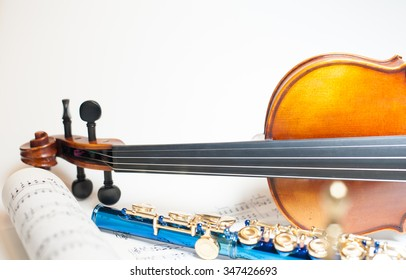 Wood violin neck detail with out of focus blue flute and score