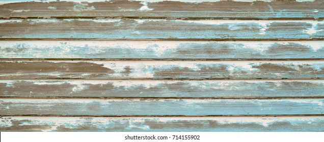 Wood wall siding or planking with rough textured chipped peeling paint.  Blue, aqua, teal and off white paint finishes worn and sanded off. Vintage texture for horizontal background.