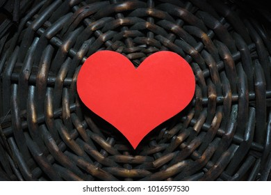 Wood weaving with a red heart.