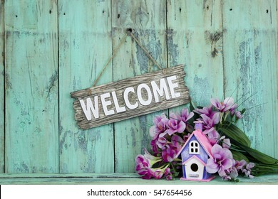Wood welcome sign by birdhouse and purple spring flowers hanging on antique rustic mint green wooden background; springtime background with copy space