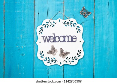 Wood welcome sign with floral border and butterflies hanging on antique rustic teal blue wooden door; family, home, love concept background
