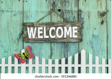 Wood WELCOME sign hanging by rope over white picket fence with colorful spring butterfly and rustic antique mint green background; springtime and home decor background with painted wooden copy space