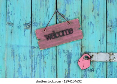 Wood welcome sign hanging on rustic teal blue wooden door with padlock; Valentines Day and love concept background