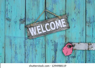 Wood welcome sign hanging on rustic teal blue wooden door with padlock; Valentines Day holiday and love concept background