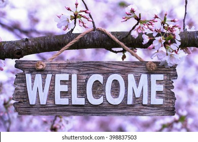Wood welcome sign hanging from spring flowering tree branch; pink and white blossoms blurred in background