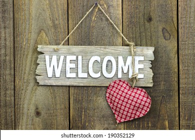 Wood welcome sign with red checkered (gingham) heart hanging on wooden fence