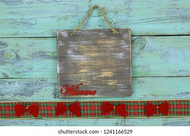 Wood welcome sign with red Christmas bows and plaid ribbon border hanging on antique rustic teal blue wooden door; holiday background with painted copy space