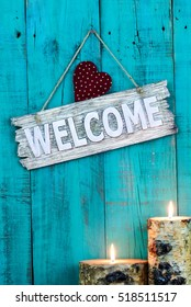 Wood welcome sign with red country heart and burning candles hanging on antique teal blue weathered rustic wooden background; holiday background with copy space