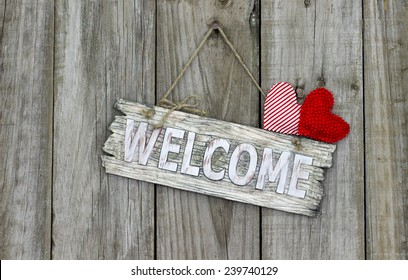 Wood welcome sign with red heart and candy cane striped heart hanging on shabby antique wooden background