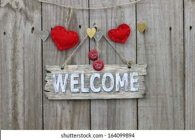 Wood welcome sign with red hearts and soda pop bottle tops