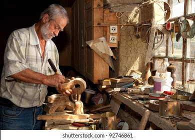 Wood worker carving wood in a derelict shed
