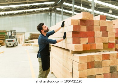 Wood worker checking a pile of wooden bars in a warehouse. Handsome carpenter grabbing a wood board to build a piece of furniture in a woodshop