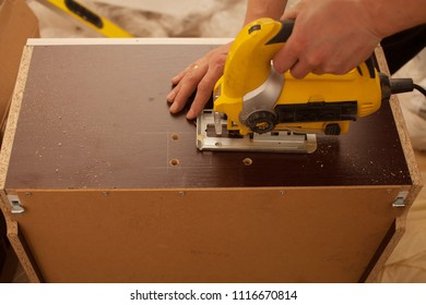 Wood worker cutting wooden panel with jig saw. DIY worker cutting wooden panel with jig saw
