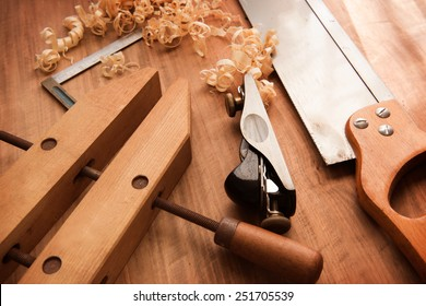 Wood working desk near the window with incandescent lighting, Wood working tools and wood shavings.