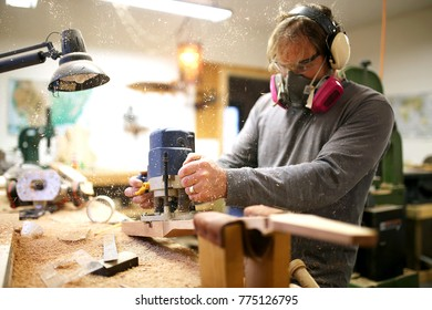 A Wood working luthier man is using a plunge router tool to build a guitar in his home workshop