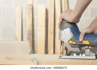 Wood working tradesman working in his shop using a cordless jig saw closeup