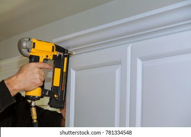 Wood working using brad nail gun to Crown Moulding on white kitchen cabinets framing trim,