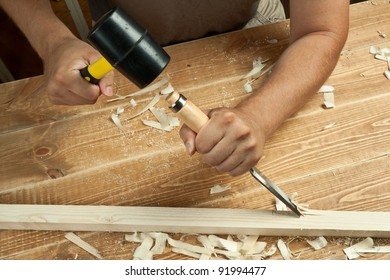 Wood workshop. Carpenter working with chisel.