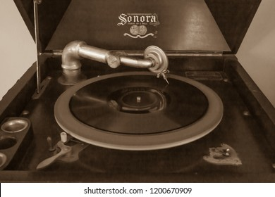 Woodbridge, New Jersey / United States - October 11, 2018: The turntable portion of an antique Sonora upright victrola is seen. A record is in motion, playing.
