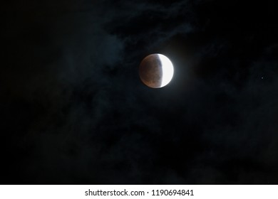 WOODBURN, OREGON - April 14, 2014:  The blood moon at the middle stage of a total lunar ellipse with a  night sky and thin cloud background in Woodburn, OR on April 14, 2014.