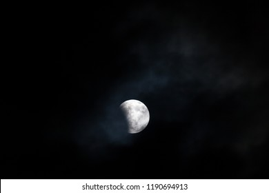 WOODBURN, OREGON - April 14, 2014:  The blood moon at the very beginning stages of a total lunar ellipse with a  night sky and thin cloud background in Woodburn, OR on April 14, 2014.