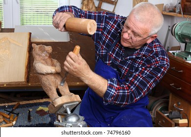 Woodcarver work in his workshop. Shallow depth of field.