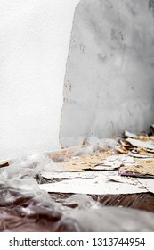 Woodchip wallpaper is removed or scraped off the wall, leftovers lie on the floor on a foil or tarpaulin, concept remodeling or renovation