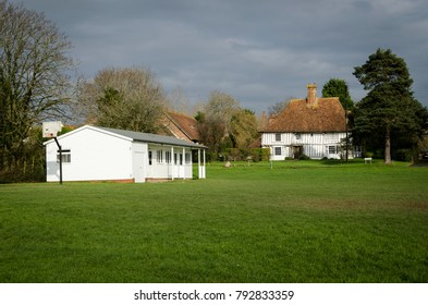 WOODCHURCH, KENT, UK, 25 JANUARY 2016 - Woodchurch cricket pavillion on the village green with an ancient half timbered cottage in the background