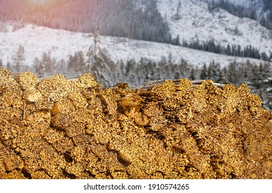 Woodcut of freshly cut lumber awaiting distribution as biomass for heating sezon. Snowy disappearing mountains in the background. - Shutterstock ID 1910574265