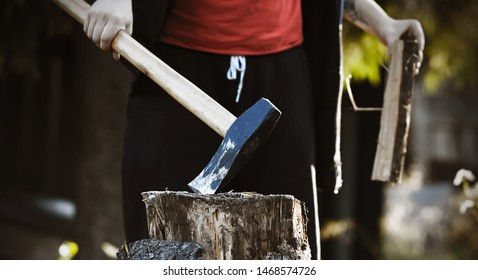 The woodcutter guy , dressed in black clothes and a red t-shirt, holds a sharp long axe in one hand, sticking it into a stump, and in the other hand he has a log.