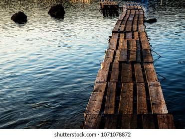 Wooded bridge in the port between sunrise